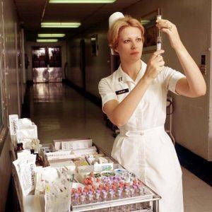A U.S. Army nurse prepares a hypodermic syringe for an injection.